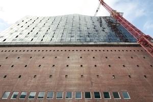 Der Blick auf die Backsteinfassade zeigt Sinterungen und Abschleifungen am Original. Bauschaden? Wertminderung? Eigenartig die Fensterreihe in Weiß. Fassadenansicht Hotel<br />