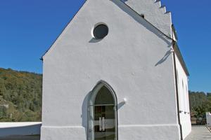 Die formal reduzierte Stahl-Glas-Konstruktion geht mit der schlichten Fassade der historischen Kirche eine gelungene Synthese ein