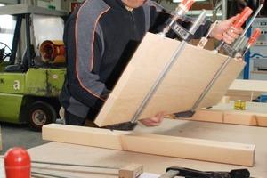 Bilder auf gegenüberliegender Seite: Die Schreiner verstehen sich auf ihr Handwerk, wie hier beim Plattenverleimen (links) und Lackieren von Türfüllungen (rechts) zu sehen