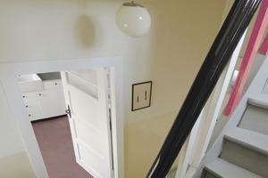 Blick ins Treppenhaus. Oben rechts ist im Bild einer der rot gestrichenen Geländerstäbe zu sehen<br />
