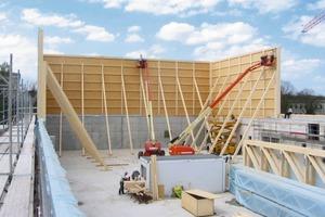 Auf das Sockelmauerwerk aus Stahlbeton stellten die Zimmerleute die 9m hohen Holztafelwände auf, die wegen der zu erwartenden Windlasten während der Montage von innen mit Streben abgestützt werden mussten