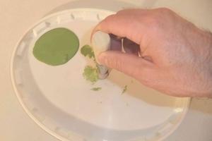 Schablonierpinsel in wenig Farbe eintauchen und auf einem Farbdeckel abtupfen