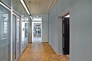 Die einstigen Gefängnisflure  wirken durch den neuen Parkettboden, die Beleuchtung und die Glasfronten einladend<br />