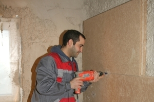Befestigung von Holzfaserdämmplatten mit Tellerdübeln auf der Innenseite einer Außenwand<br />Foto: Pavatex