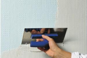 Arbeitsablauf: Spachtel mit 4-mm-Zahnkelle auftragen, Maler-Universalvlies lotrecht einlegen und mit einer Glättkelle andrücken. Nächste Bahn etwa 5 cm über die Vorherige überlappend ansetzen und andrücken. Beide Bahnen im überlappenden Bereich in der Mitte durchschneiden und die beiden abgeschnittenen Streifen entfernen. Mit der Glättkelle andrücken und mit dem Schwammbrett nacharbeiten. Nach Trocknung kann die Fläche mit lösemittelfreiem Tiefengrund gestrichen werden<br />
