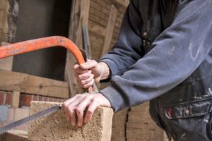 Zusägen von Lehmziegeln für die Ausfachungen