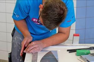 """Raphael Rossol, Goldmedaillengewinner im Gewerk der Fliesen-, Platten- und Mosaikleger, schleift passgenau ein Stück Fliese für ein Mosaik <span class=""""bildnachweis"""">Fotos (2): Thomas Wieckhorst</span>"""