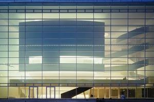 Hinter dem gläsernen Vorhang des Gütersloher Theaters setzen sich die beiden Hauptdarsteller gut in Szene: der schwebende Theatersaal (links im Bild) und die nach oben breiter werdende Spiraltreppe (rechts im Bild)<br />