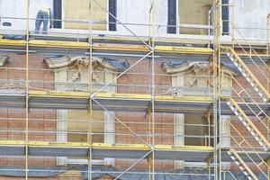 Um die historischen Schlossfassaden detailgetreu nachzubilden, wird vor dem bereits erstellten Betonbau jeweils eine komplette Mauerziegelwand als Vorsatzschale hochgezogen, die mit den Natursteinornamenten durchzogen ist und anschließend verputzt wird
