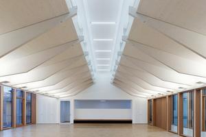 Der Ratssaal im Obergeschoss des Zwischenbaus wird von zwei filigranen Schmetterlingsdächern überspannt, die von 22 Schwertern aus Fichtenholz getragen werden<br />Foto: Zooey Braun