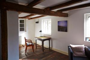 Arbeitstisch im Wohnzimmer. Der historische Dielenboden wirkt homogen. Das linke Fenster blickt auf die Probsteimauer