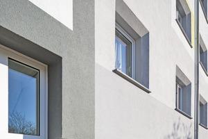 Der Sockelbereich mit dem Kellergeschoss ist durch die dünnere Dämmschicht leicht zurückgesetzt. Das Gebäude bekommt eine elegante Leichtigkeit, die grauen Farbtöne geben Halt