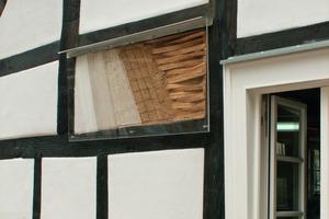 Oben links: Der Schichten- aufbau im Schaugefach – ausgezäuntes Fachwerk mit aufgerautem Lehmbewurf, zweilagiger Oberputz, Anstrich (Kalkkaseinmilch)