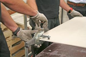 Auf dem Schneidetisch brechen die Handwerker die Fliesen