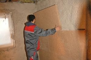 """<div class=""""99 Bildunterschrift_negativ"""">In den frisch aufgetragenen Putz legten die Handwerker direkt die Holzfaserdämmplatten ein</div>"""