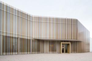 Der Eingang des Museums setzt sich durch seine gold- und messingfarben gebänderte Fassade gegen das Weiß des kubischen Gebäudes ab<br />Fotos: Heradesign