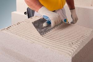 Der Klebemörtel wird mit der Zahntraufel vollflächig auf die Mineraldämmplatten aufgetragen<br />