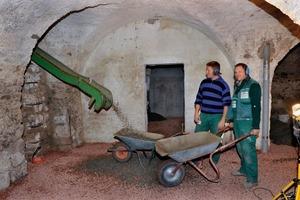 Die Handwerker bringen in den westlichen Gewölbekeller eine kapillarberechende Ausgleichsschüttung ein