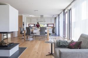 Lebensmittelpunkt der dreiköpfigen Familie ist der nach Westen ausgerichtete, offen gestaltete Wohn-, Ess- und Kochbereich mit seinen vielen Fensterelemente zu allen Seiten