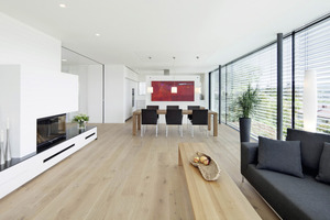 Das Obergeschoss wird von einem großzügigen Wohn-Essraum bestimmt. Eine frei stehende Wandscheibe trennt diesen Teil von der Küche ab<br />