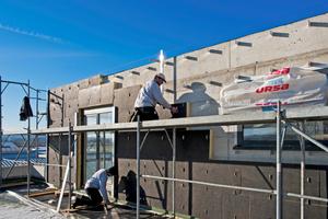 Vor dem Anbringen der Fassadenbekleidung aus duromeren Hochdrucklaminaten wurden an den Obergeschossen Dämmplatten aus Glaswolle montiert