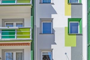 Balkonbrüstungen, Fensterleibungen und die Farbflächen über dem Eingangsbereich bilden ein harmonisches Ganzes, sie integrieren die Wärmedämmung optisch und lockern die Fassade auf