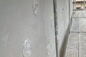 Die noch von etwas Putz überdeckten Leuchtröhren in der Fassade kurz vor Abschluss der Putzarbeiten