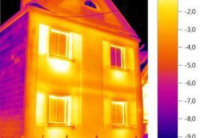 Wärmebild eines Hauses. Schwachstellen werden mit Hilfe einer Wärmebildkamera sofort sichtbar: Heizkörpernischen sind nicht richtig gedämmt, Reflexion vom kalten Himmel im rechten oberen Fenster