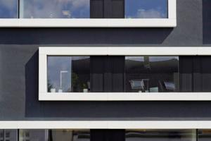 Aus der dunklen Fassade treten die weiß pulverbeschichteten Metallumrahmungen der Fensterbänder plastisch hervor<br />Foto: Christian Eblenkamp