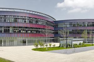 Um die runde, gekurvte Form des neuen Gymnasiums in Bochum zu stärken und den fließenden Eindruck der organisch geschwungenen Linien zu unterstützen, gliedert sich die Fassade horizontal