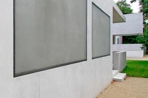 Die Fenstergläser reflektieren wie der lasierte Beton die Farben des Himmels