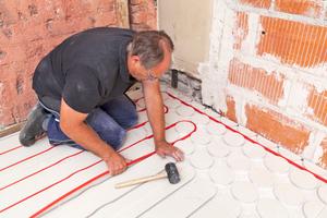 In einer zweiten Schicht kann man Gipsfaserplatten mit vorgefrästen Vertiefungen für eine Fußbodenheizung verlegen