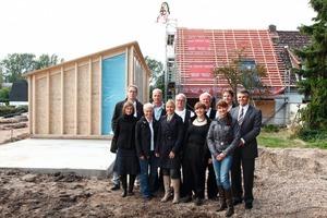 Rechts: Am 17. September war Richtfest. Ein Teil der Erweiterung in Holzbauweise steht bereits (links im Bild). Im Bildvordergrund die Velux-Mitarbeiter, Architekten und Handwerker<br />