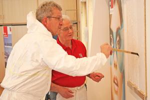 Mitarbeiter der Firma Baumit erklärt einem Kongressteilnehmer die Herstellung einer Rindenrelief-Struktur