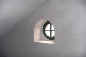 Wandabschnitt mit rundem Fenster im Anbau R nach Abschluss der Sanierungsarbeiten