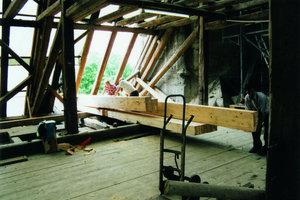 """<div class=""""2.6 Bildunterschrift"""">Darunter: Sanierungsarbeiten an den Fundamenten und am Dachstuhl. Die stark geschädigte Holzkonstruktion musste zur Reparatur der Mauerkrone abschnittsweise angehoben werden</div>"""