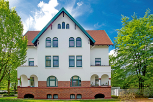 Nachher: Auf solidem Klinkersockel erhebt sich ein vielgestaltiges energieeffizientes Mauerwerk mit weißem Anstrich und in Grün gehaltenen Fenstern
