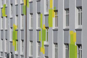 Die straßenseitige Fassade des Wohnblocks zeigt sich in edlen Grautönen, die die Schmuckelemente betonen und fröhlich-aufglockerten Farbflächen