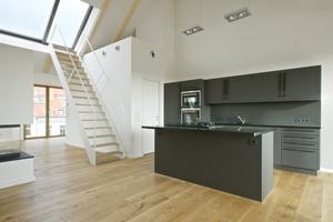 Die zweigeschossige Maisonettewohnung ist als offen gestalteter Grundriss mit großzügiger Küchenzeile und Kochinsel konzipiert, die mittige Maschinentreppe führt auf die oberste Dachterrasse