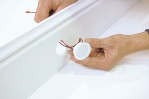 Nach dem Einsetzen der LED-Spots in die Leiste muss der Handwerker die Kabel verbinden. Danach kann der Kleber auf der Rückseite aufgetragen und die Leiste montiert werden<br />