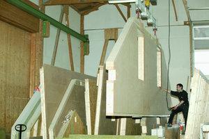 Für Holztafel- und Holzrahmenbauten werden die Elemente in der Regel in der Zimmerei vorgefertigt und mit dem LKW zur Montage auf die Baustelle geliefert
