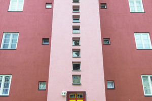 Ein vorspringendes, in hellem Rot gefasstes Treppenhaus mit einem vertikalen Band kleiner quadratischer Fenster<br />