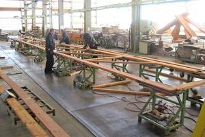 Oben: Fertigung von Nagelplattenbindern in der Zimmerei. Die Nagelplatten werden auf die Holzteile gelegt und mit hydraulischen Pressen oder Walzen eingepresst