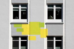 Im Detail zeigt sich die ausgeklügelte Farbgestaltung mit insgesamt sieben Grautönen und die passenden Akzente in Grün und Gelb, die wie Blüten wirken. Weiße Möwen aus dem Logo der Wohnstätten Cuxhaven eG lockern das Bild zusätzlich auf