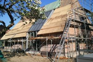 Rechts: Fest verglaster Ausschnitt aus der Gebäudehülle auf der Nordseite mit zum Teil bereits mit Reet gedecktem Dach<br />