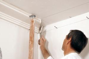 Montage vorgefertigter Stuckprofile am Übergang zwischen Wand und Decke