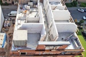 Die Baustelle aus der Luft: Auf das mit neunen Innenwänden und Zwischendecke gefüllte Gebäude setzten die Zimmerleute den neuen Dachstuhl auf<br /><br />