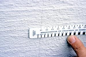 Ein etwa 0,1 mm breiter Riss mit Rissbreitenmaßstab