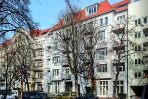 Hinter Bäumen versteht: Die mit einem hydroaktiven mineralischen WDVS energetisch sanierte Fassade einer typischen Kreuzberger Parzelle aus dem Jahr 1909
