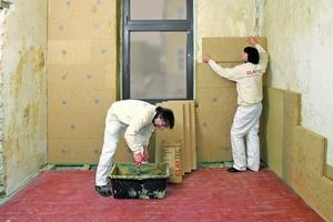 Montage einer Innendämmung aus Weichfaserplatten: Der Lehmmörtel wird angemischt, die Platten rechts neben dem Fenster zur Vermaßung angehalten und im Anschluss auf Dreiviertel zugeschnitten